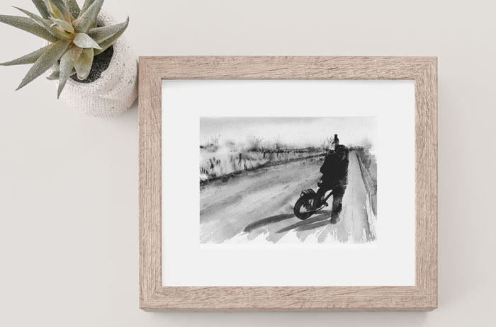 Link to Country Roads page. Photo of framed painting of bicyclist on a road. Painting lying on a table.