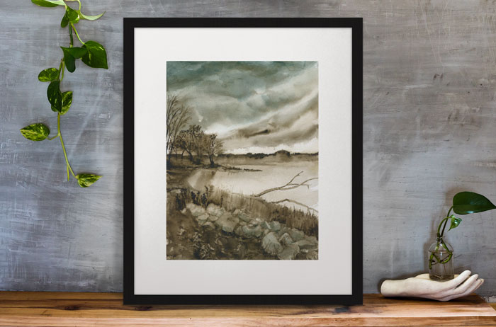Photo of painting of rocks and trees by a waterfront in a frame leaning against a wall.