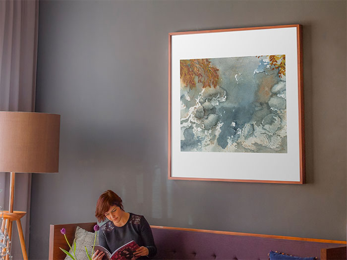 Photo of painting of an icy stream with orange leaves above it. The painting is hanging on a wall.