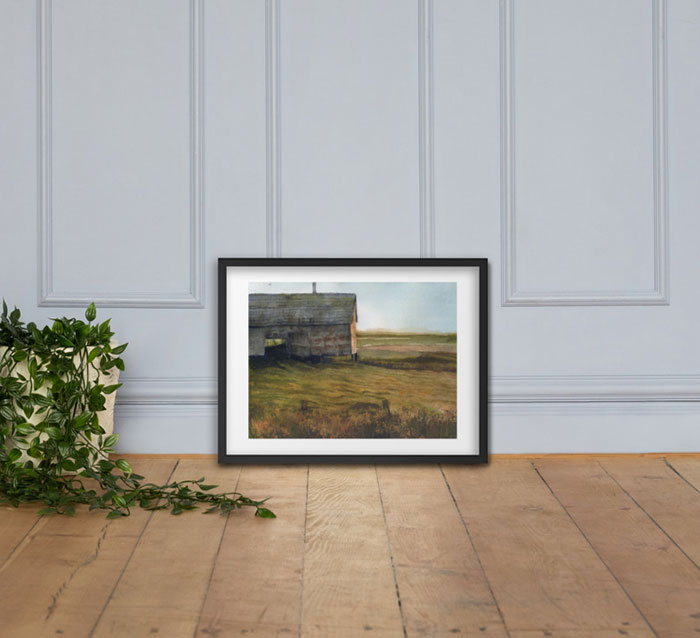 Photo of framed painting of an old barn leaning against the wall, next to a plant.