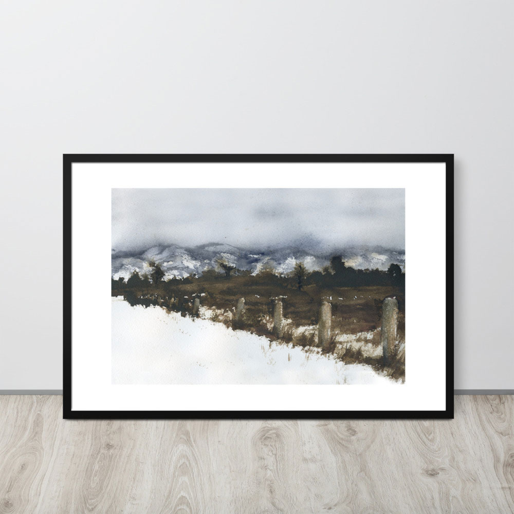 Photo of framed painting of a snowy field. Painting leans against a wall.