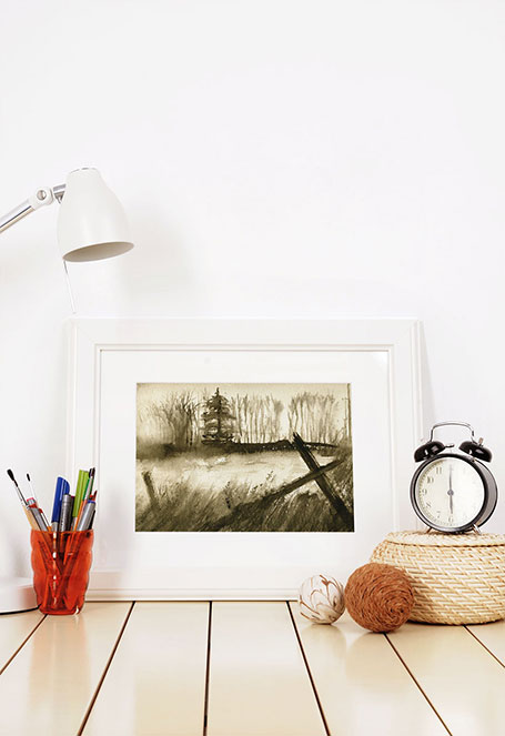 Photo of a painting of a field leaning against a wall.
