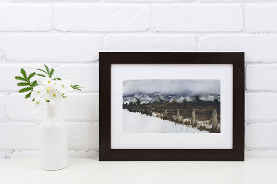 Photo of framed painting of a snowy field. Painting leans against a wall next to flowers.