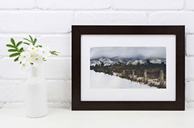 Link to Winter Breaking Page. Photo of framed painting of a snowy field. Painting leans against a wall next to flowers.
