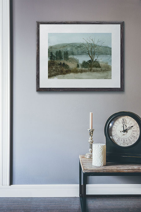 Photo of a painting of a field and river on a wall.
