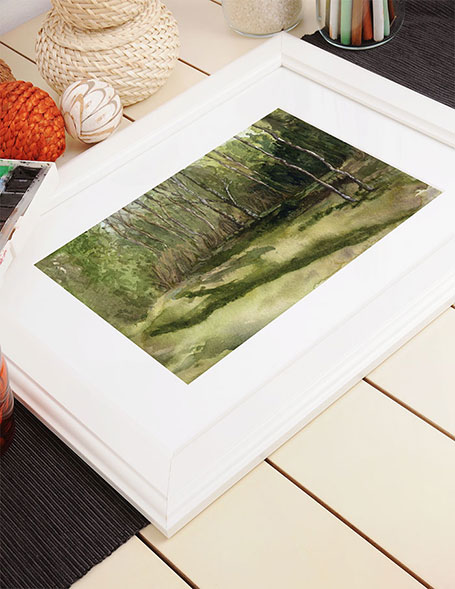 Photo of painting of summer trees in a frame laying on a table.