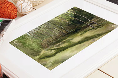 Link to Summer trees page. Photo of painting of summer trees in a frame laying on a table.