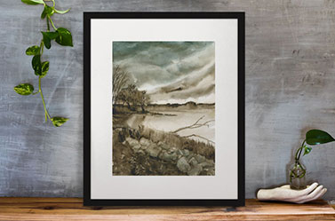 Link to Waterfront page. Photo of painting of rocks and trees by a waterfront in a frame leaning against a wall.